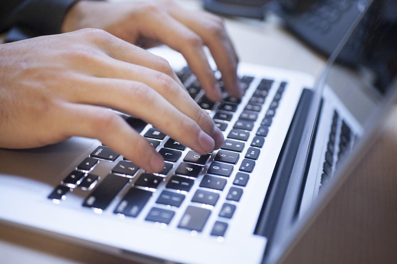 personne tapant sur son clavier d'ordinateur