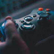 Un gamer tient une manette dans la main.