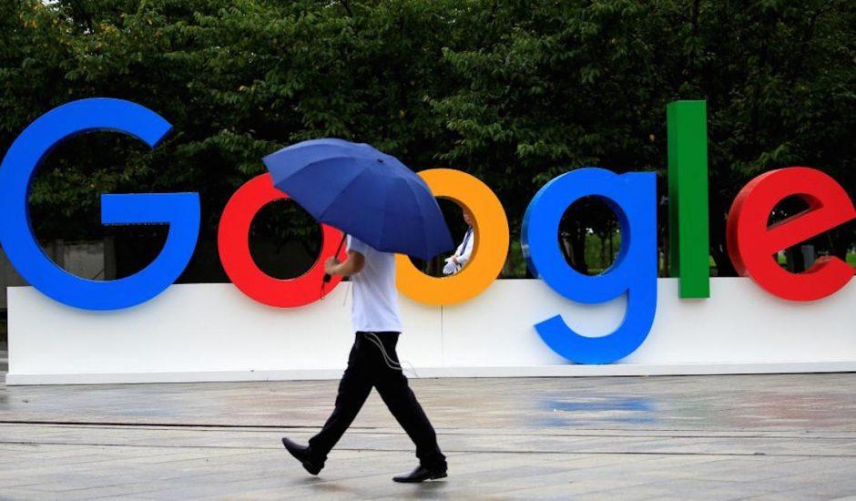 Une personne avec un parapluie marchant à côté du logo de Google