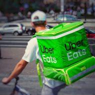 Un livreur avec un sac à dos Uber Eats à vélo dans la rue.