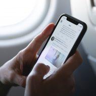 Une personne dans un avion utilisant Twitter sur son Smartphone