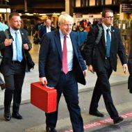 Le premier ministre britannique, Boris Johnson, marche dans la rue accompagné de ses conseillers.