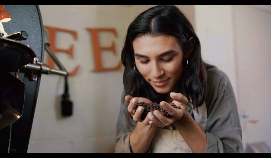 Une femme tenant et reniflant des graines de café