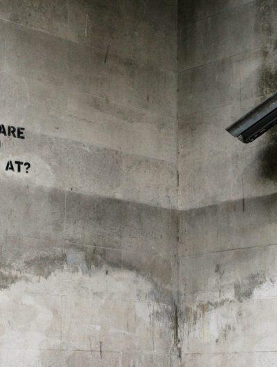 """Caméra de surveillance observant un message écrit sur un mur, et qui dit : """"What are you looking at?"""""""