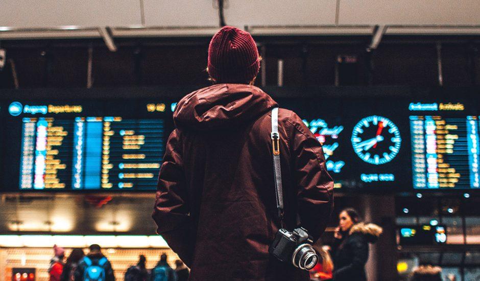 Aéroports : un homme face à un tableau des horaires.