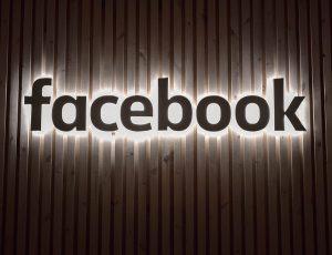 Le logo illuminé de Facebook sur un mur en bois.