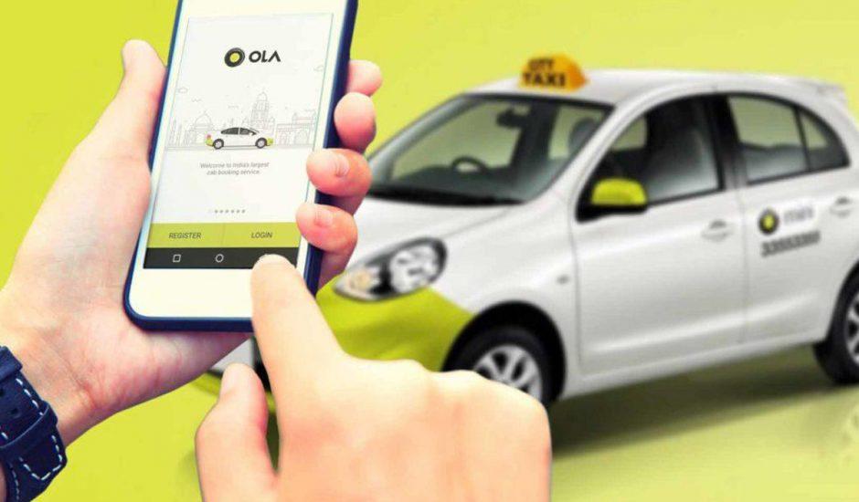 Ola : l'application VTC lancée sur un smartphone devant une voiture de la firme.