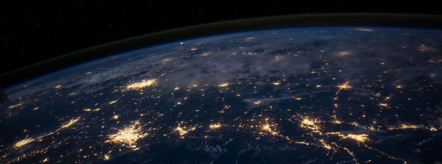 Une photo de la Terre de nuit, on voit les villes éclairées depuis l'Espace