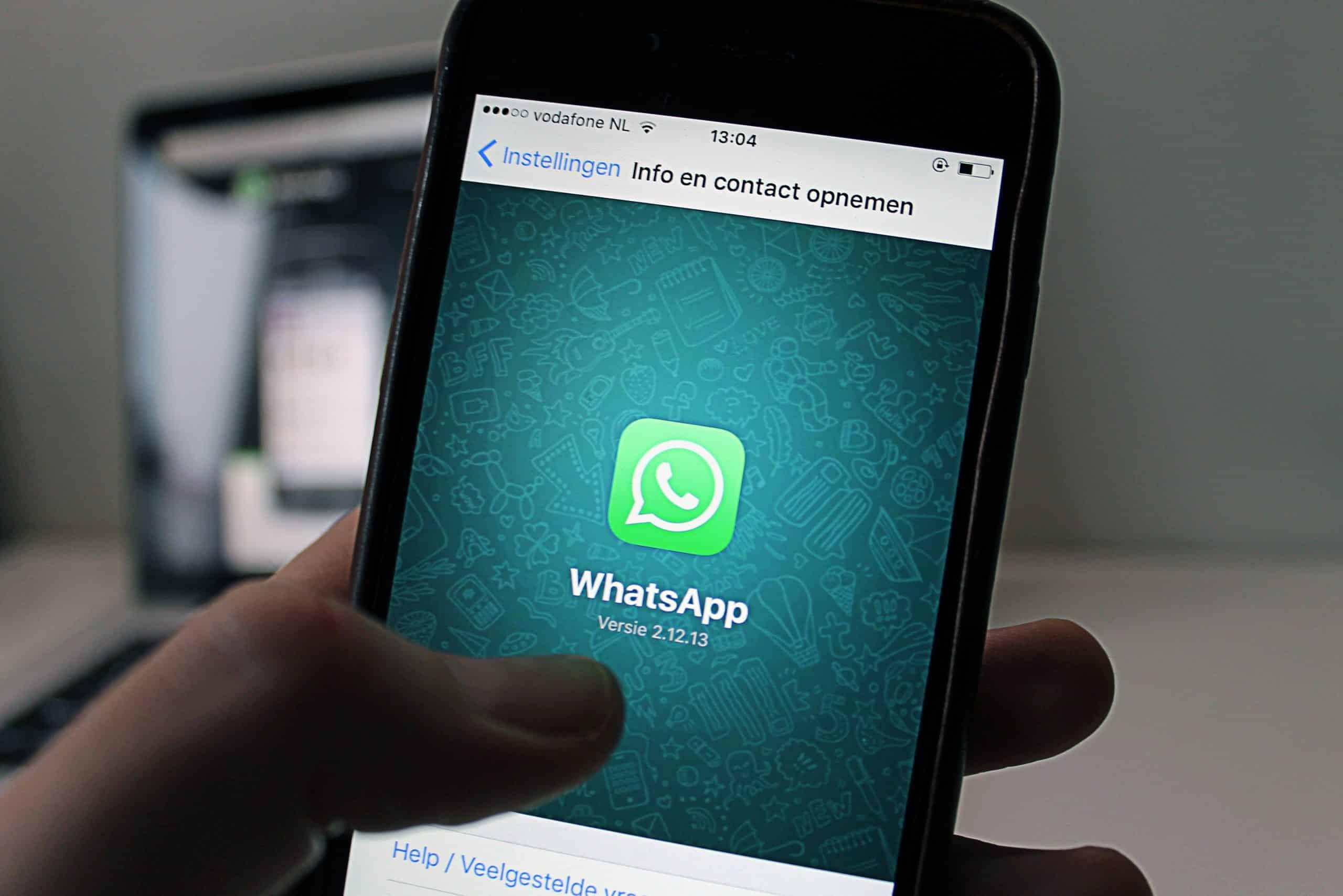 Une personne tient un smartphone sur lequel s'affiche le logo de WhatsApp.