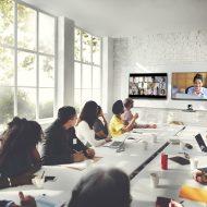 Des personnes autour d'une table de réunion participant à une visioconférence