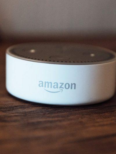 Un appareil Echo Dot d'Amazon posé sur une table en bois.