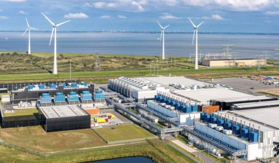 Un centre de données de tient devant un champ d'éoliennes.