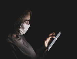 Une femme avec un masque chirurgical regardant son téléphone
