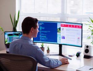 Un homme en chemise grise assis sur une chaise devant un écran d'ordinateur