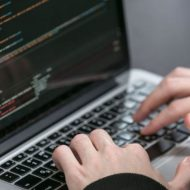 Une personne tapant des lignes de code sur son ordinateur