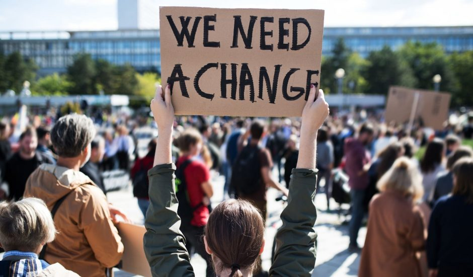 """Une manifestante tenant un paneau """"We need a change"""""""