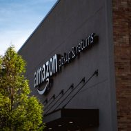Un entrepôt Amazon devant lequel se trouve un arbre.