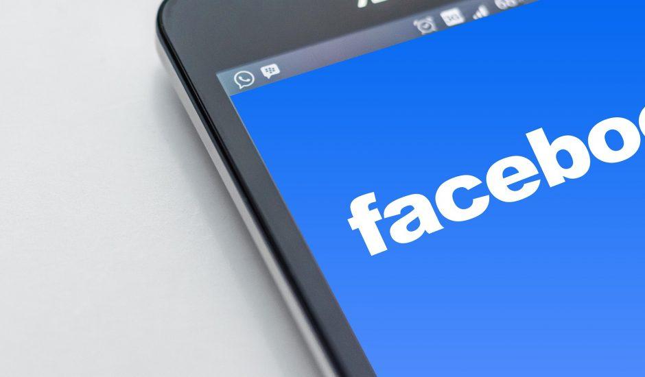 Un smartphone posé sur une table avec l'écran bleu de Facebook.
