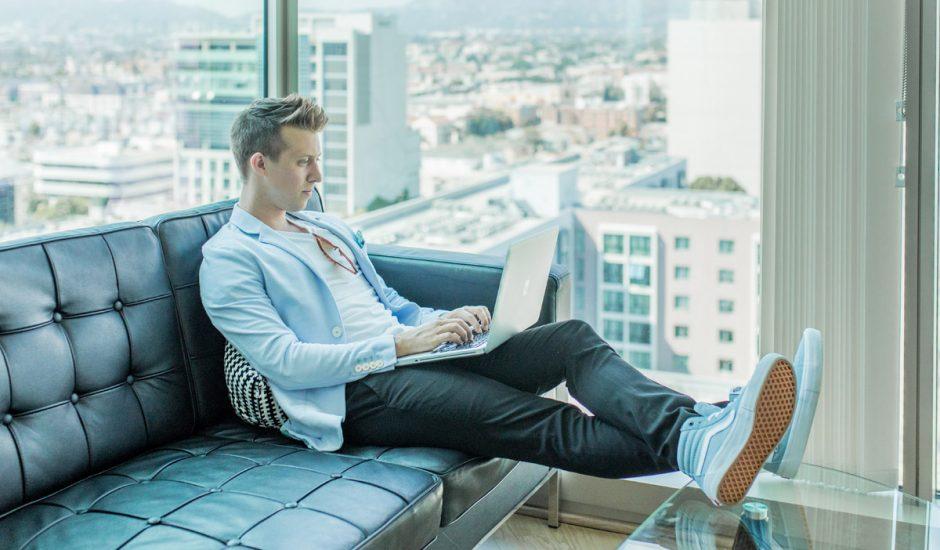 Un homme assis sur un canapé qui travaille sur son ordinateur.
