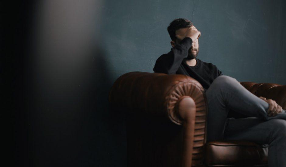 Un homme assis sur un fauteuil se tenant le visage.