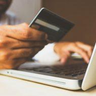 Un homme payant un achat sur internet avec sa carte de crédit.