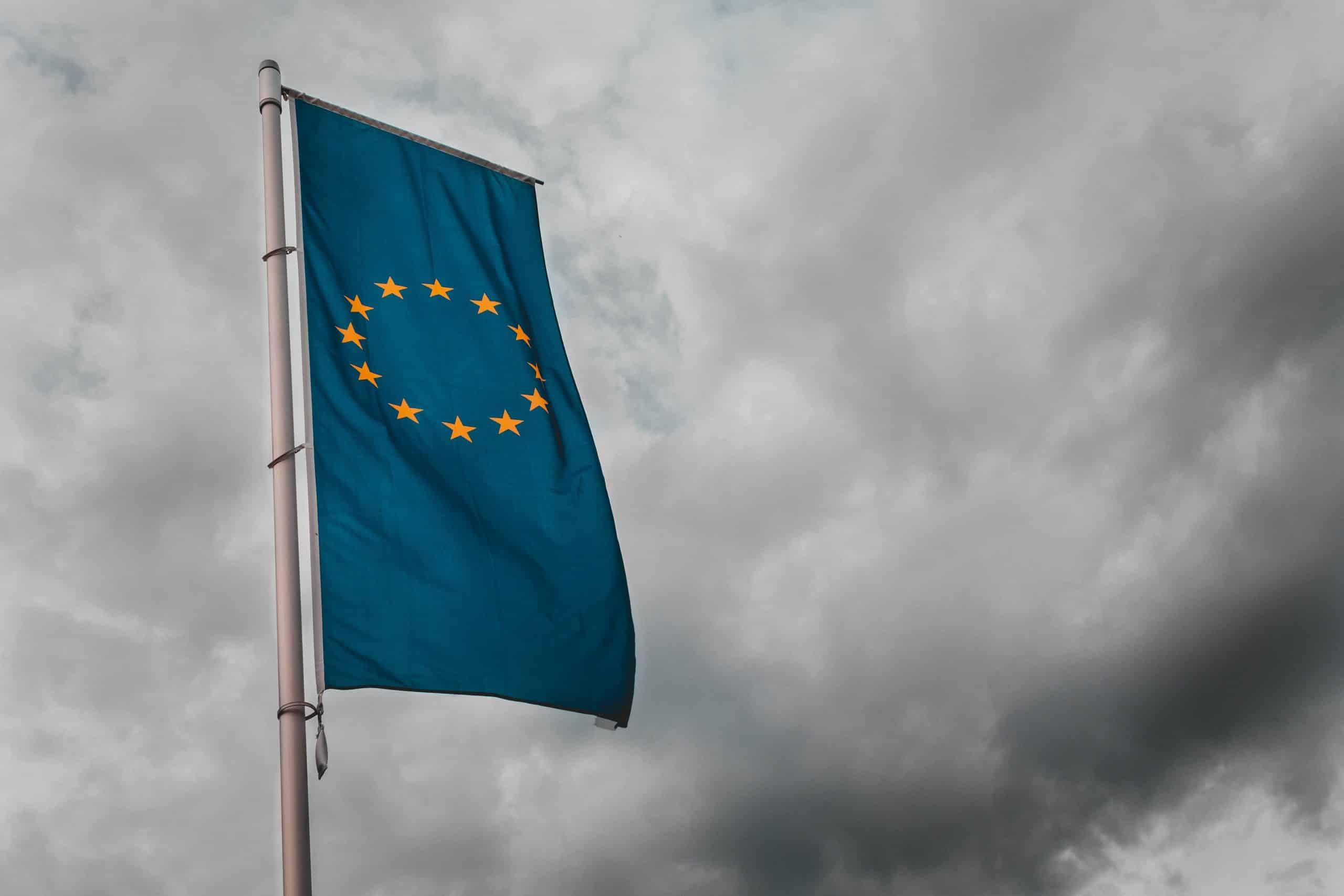 Un drapeau de l'Union Européenne flottant dans un ciel nuageux