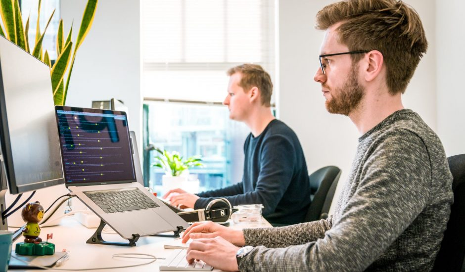 Deux hommes travaillant sur ordinateur.