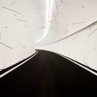 L'intérieur d'un tunnel de The Boring Company, avec une route entourée de parois blanches et futuristes.