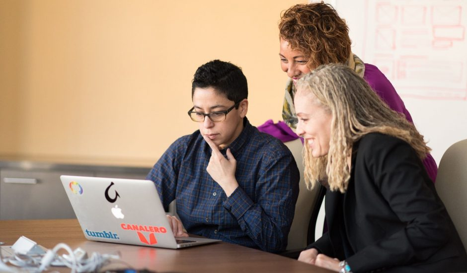 Trois personnes consultant un ordinateur