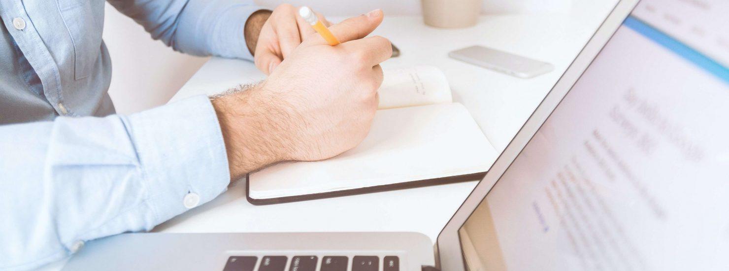 Un homme prenant des notes devant son ordinateur