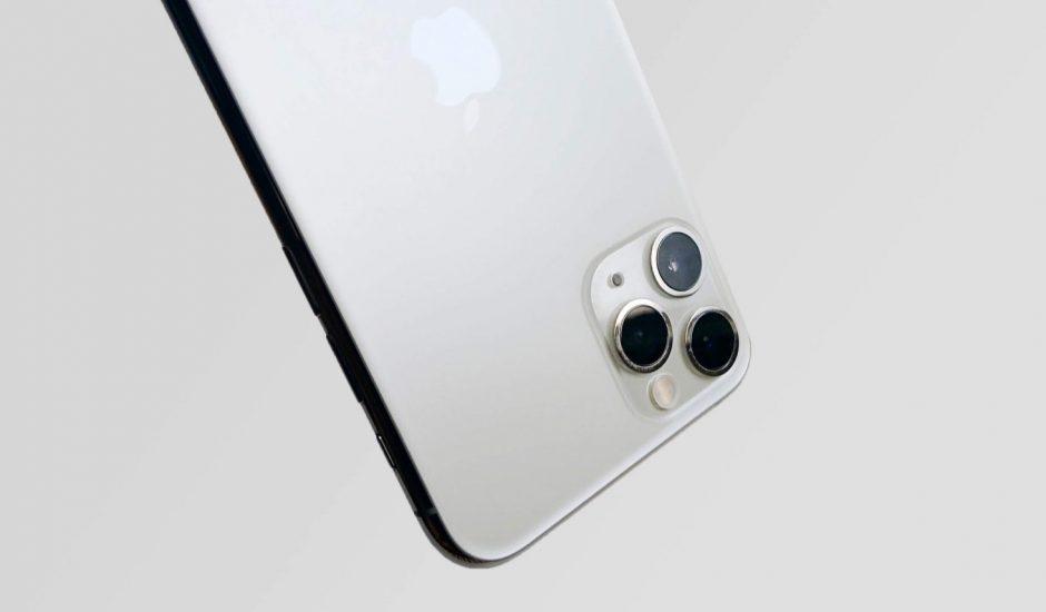 Un iPhone 11 Pro à l'envers sur un fond gris.