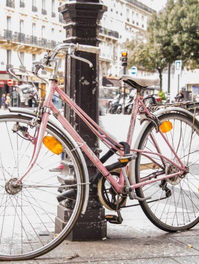 Un vélo rose accroché à un poteau dans les rues de Paris.