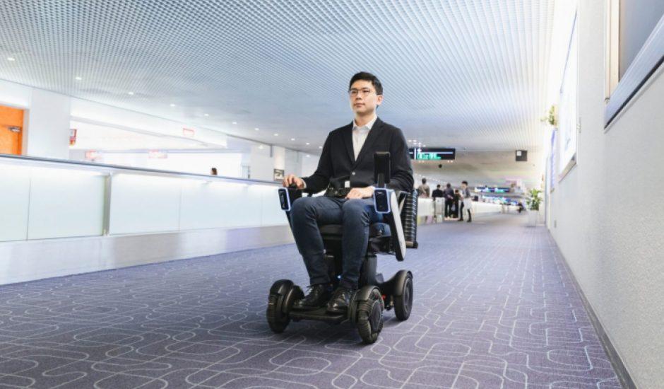 Un homme assis sur un fauteuil robotisé WHILL dans un aéroport.