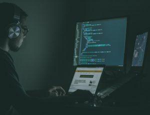 Un chercheur en cybersécurité travaille à son bureau face à plusieurs écrans.