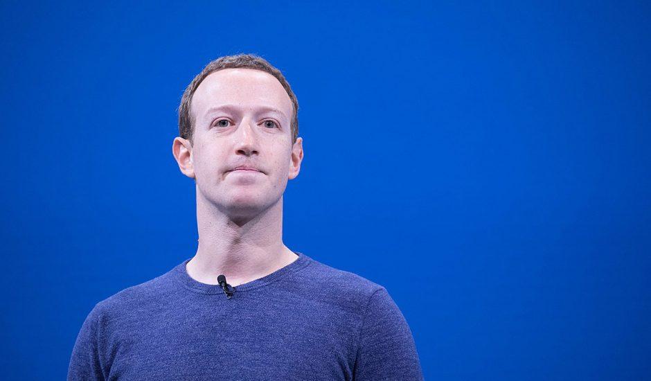 Portait de Mark Zuckerberg se tenant devant un fond bleu.