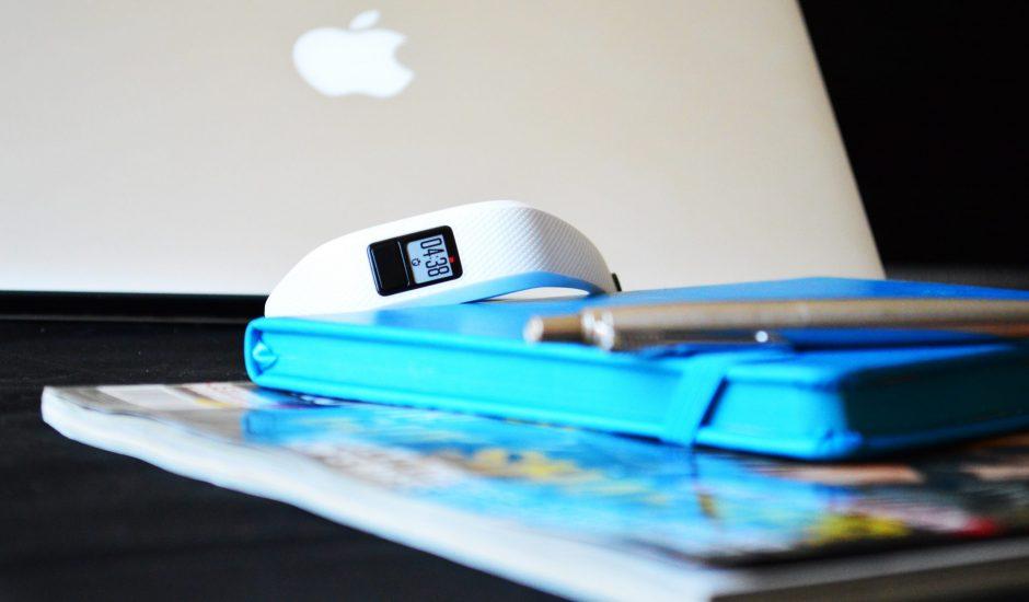 Une smartwatch blanche posée sur un carnet