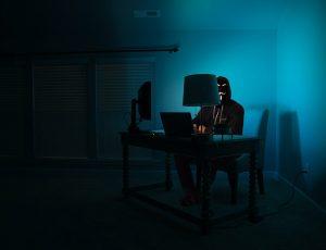 Un Anoymous assis à un bureau.