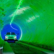 Une voiture Tesla blanche roule dans un tunnel.