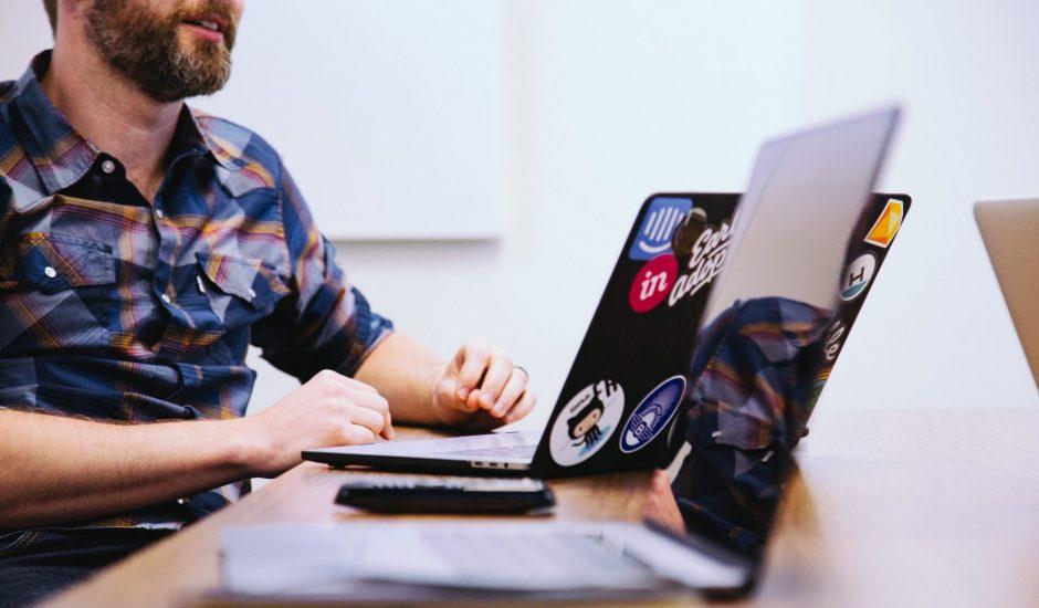 un employé dans une salle de réunion devant son ordinateur