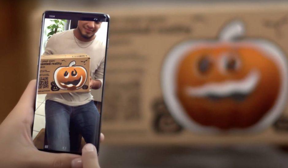 Un smartphone prend en photo l'image d'un emballage d'Amazon sur lequel se trouve un dessin de citrouille Jack O' Lantern.