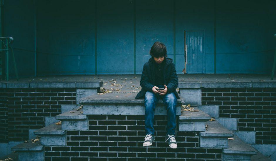 Un petit garçon consultant Instagram sur son smartphone.