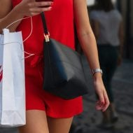 Une femme portant un sac H&M dans la rue.