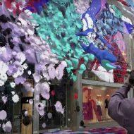 Un homme projette de la peinture sur la façade de bâtiments grâce à son smartphone.