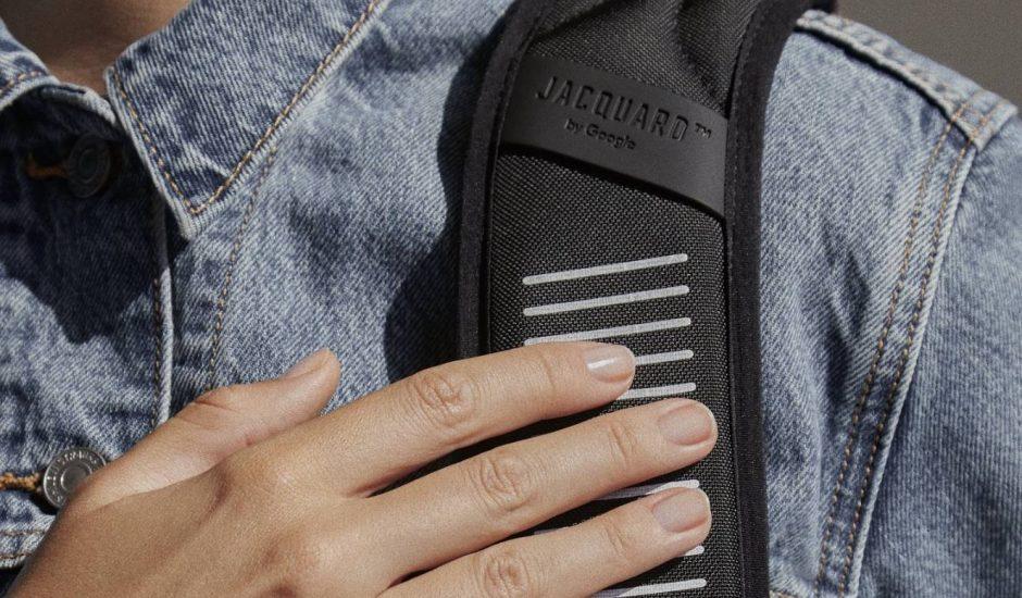 Une main touche la bretelle tactile d'un sac à dos Konnect-i.