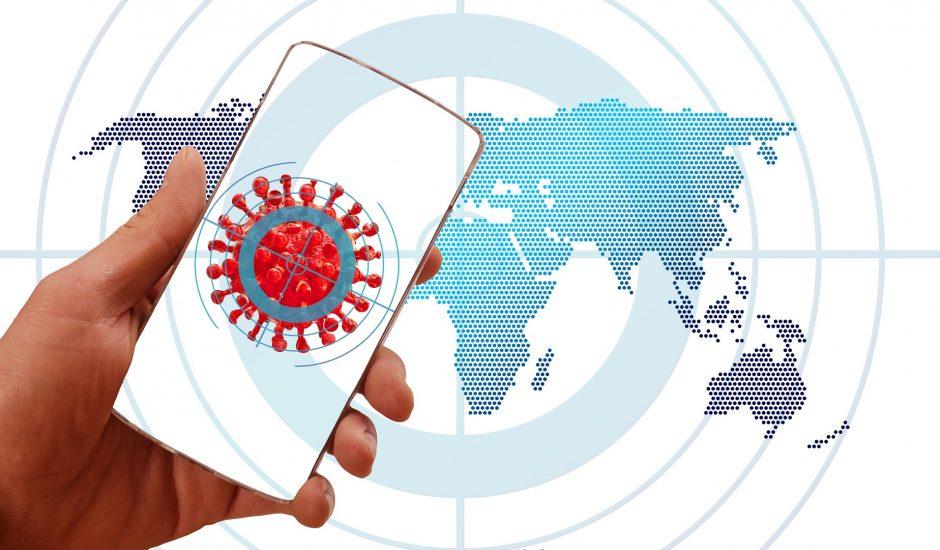 Une homme tient un smartphone ouvert sur une image du coronavirus.