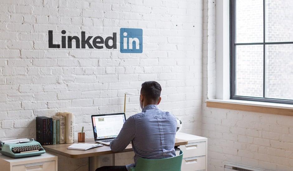 Un homme assis à son bureau avec le logo LinkedIn sur le mur.