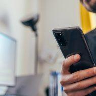 Un homme tient son smartphone dans la main.
