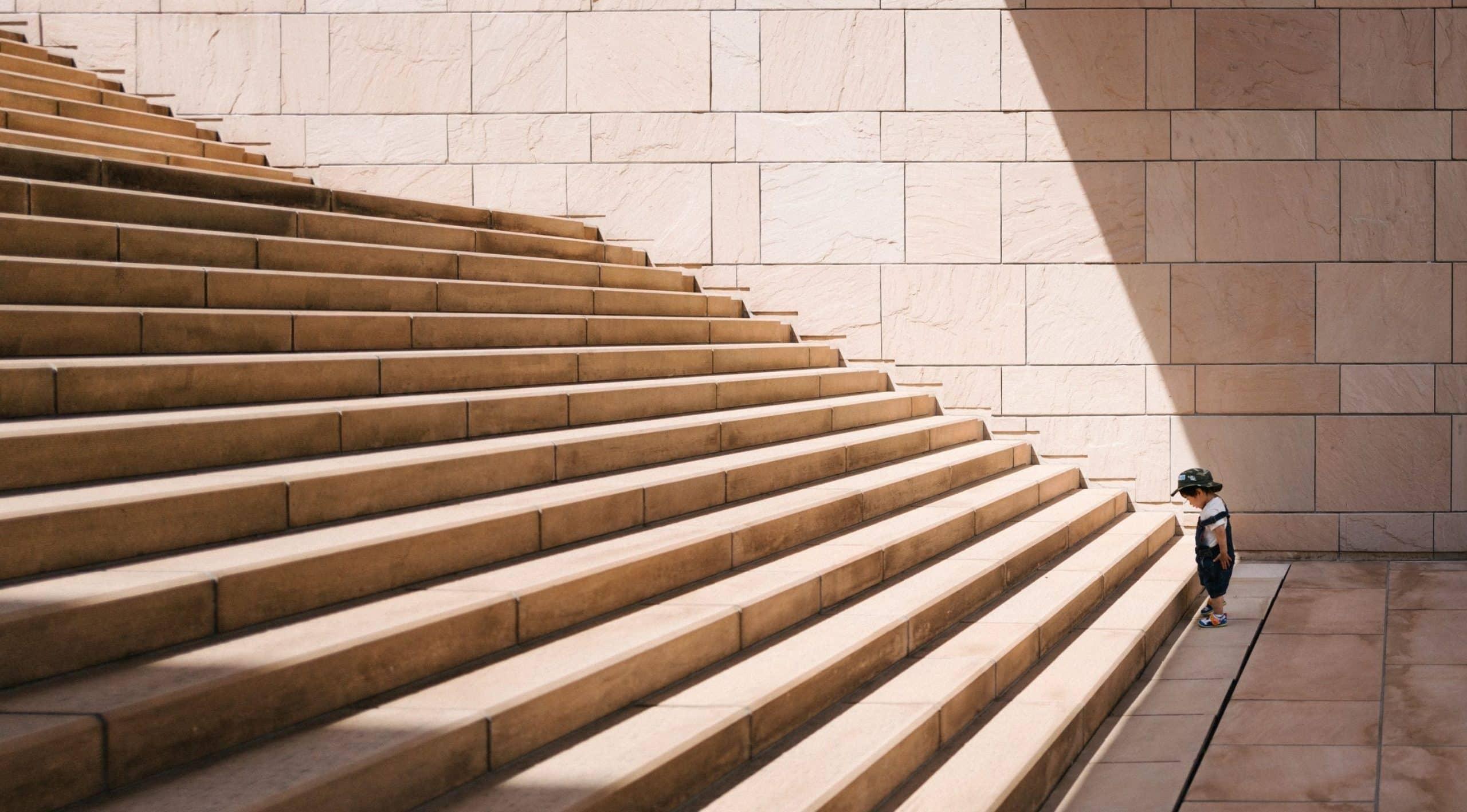 un gamin en face d'un escalier