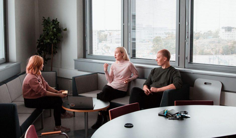 trois employés travaillant et échangeant