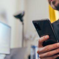 Un homme tient un smartphone dans la main.